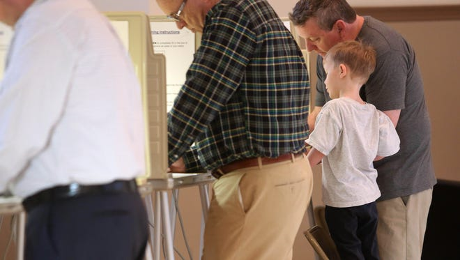 A boy watches his father vote in the Ohio primary at the Terrace Park Community Building on Tuesday morning.