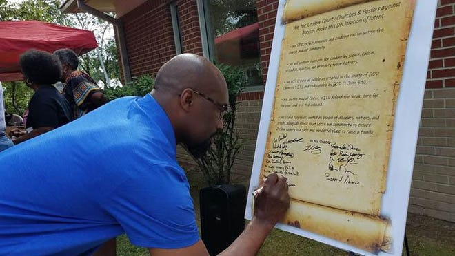 Pastor Sheldon Taylor of Sinai Christian Center Church of Richlands signs a Declaration of Intent by the faith community against racist during a Tuesday prayer meeting in Richlands.