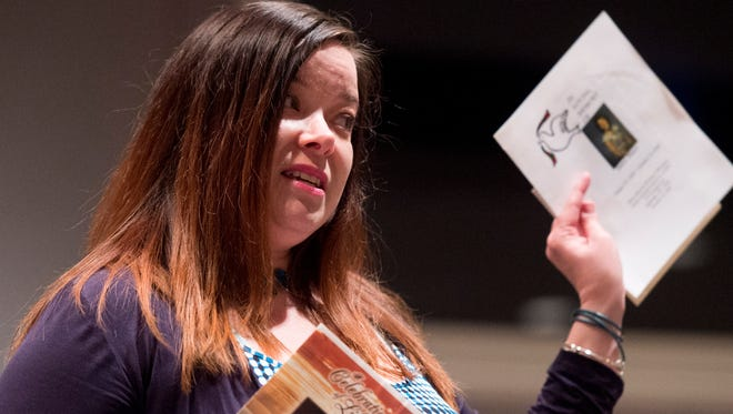 Brandy Mayo, of Nashville, holds up the funeral programs from four family members who died from addiction while speaking during The Tennessean's Opioid Epidemic Forum on Wednesday, June 15, 2016, at the First Amendment Center in Nashville.