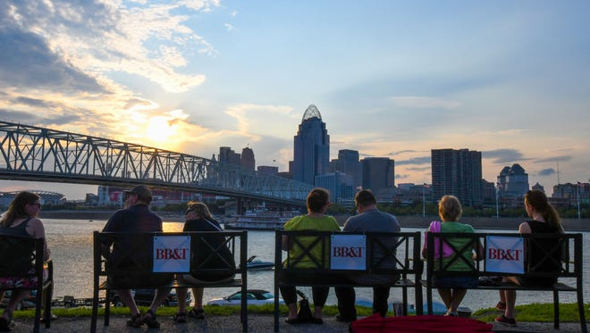 Festival-goers watch the sun set over the Cincinnati skyline during the first day of Glier's Goettafest Thursday, August 3, 2017, in Newport.