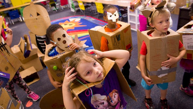 Amelia Mills, front center, and her kindergarten classmates line up to sing a song before their costume parade at Delaware Elementary School Monday afternoon. The kids had created their own cardboard costumes as part of a STEM-based global Cardboard Challenge.