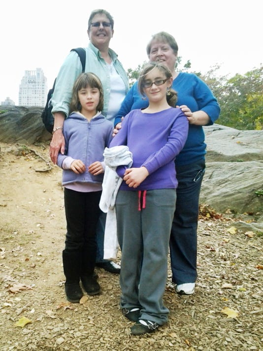 This October 2012 photo provided by Marianne Duddy-Burke shows her, background right, with her wife, Becky Duddy-Burke and their daughters Infinity, foreground left, and Emily in New York's Central Park.