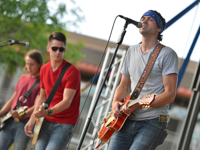 Emerging Central Minnesota artist Jeremiah James Korfe (right) belts out a variety of country and rock for the crowd of thousands gathered Thursday night at Joetown Rocks in St. Joseph.