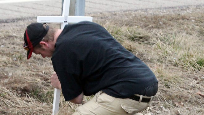Jason May, father of 13 month-old twins Sean and Samantha, erects a cross   near the spot where the children were killed.