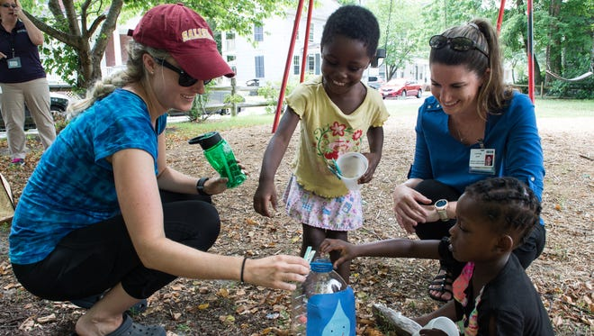 Marie Koehne, left, and Caitlyn Daw, of Peninsula Regional Medical Center's Weight Loss and Wellness program, teach two neighborhood kids a game involving dropping a clothespin into a water jug at the Newton/Camden Tot Lot on Monday, June 19, 2017. The game is designed to teach kids that they should be drinking six cups of water a day.