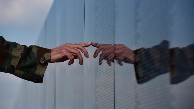 Vietnam vet Art Woolis searches for the names of high school buddies he lost during the war at The Moving Wall, a traveling half-size replica of the Vietnam Veterans Memorial, on display in May at Overpeck Park.