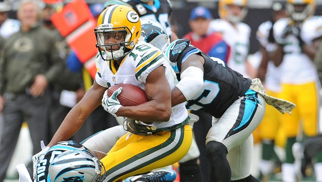 Green Bay Packers wide receiver Randall Cobb gets wrapped up after making a catch during Sunday's game against the Carolina Panthers in Charlotte, N.C.