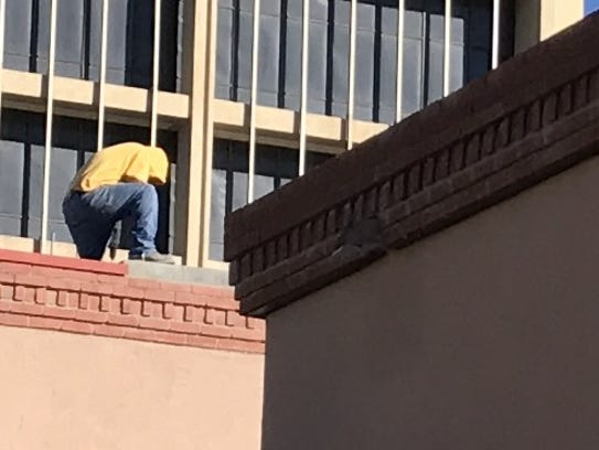 A construction worker does work on the roof of the