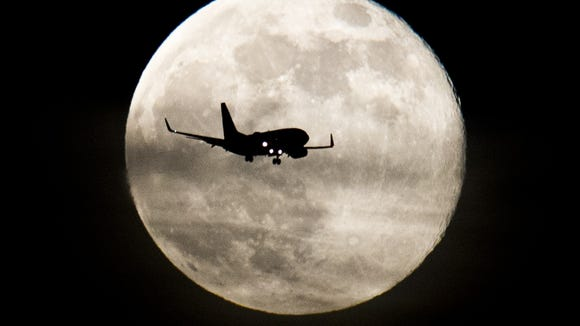 A supermoon looms large in June 2013 as a plane makes its way to Phoenix Sky Harbor International Airport.