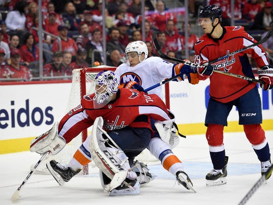 New York Islanders left wing Anders Lee, center, gets wrapped up with Washington Capitals goalie Braden Holtby (70) while right wing Alex Chiasson stands at right during the second period of an NHL hockey game, Thursday, Nov. 2, 2017, in Washington. (AP Photo/Nick Wass)