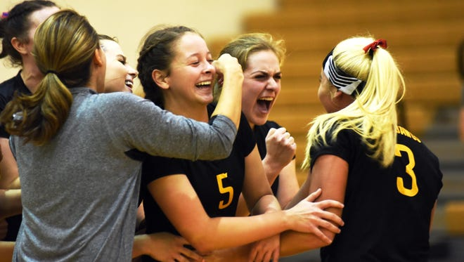 """Tri-Valley players, including Reagan Baughman, left, Janessa Dawson and Kearstin """"Utie"""" Dumolt, celebrate after earning the deciding point in a five-set win against John Glenn on Tuesday."""