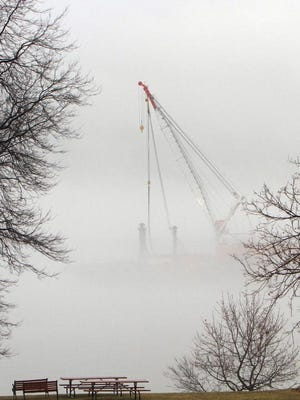 A Tappan Zee Bridge construction crane is seen  through the fog from Nyack.