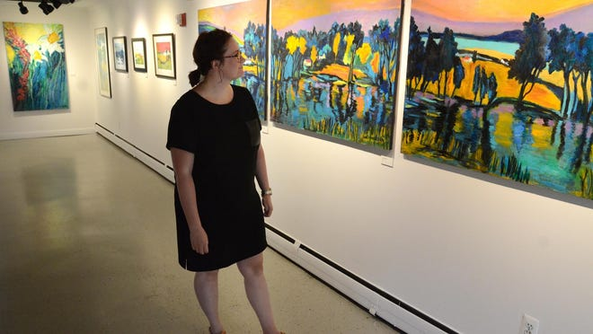 Director Abigail Wright-Geddes takes a look at some of the paintings on display at the Northville Art House on Cady St. on Aug. 20. Northville has a few art houses and galleries which apparently means its a snobby locale.