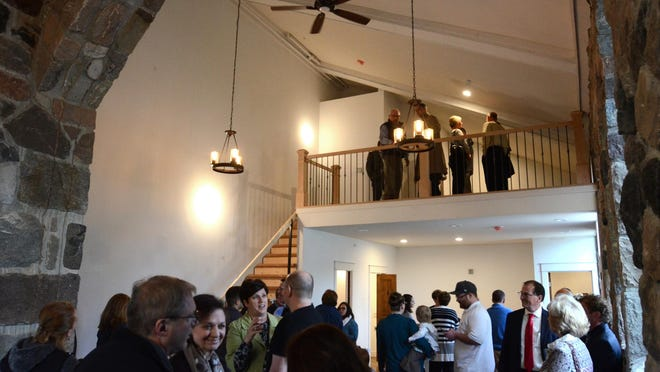 Visitors gather in the main room of the Bell Tower condos during its grand opening celebration.