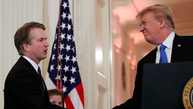 President Donald Trump shakes hands with Judge Brett Kavanaugh his Supreme Court nominee, in the East Room of the White House.