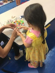 A young participant works with beads in The Shelter's on-site day care. The curriculum includes academic readiness activities as well as socialization and encourages children to share their feelings and safety plan.