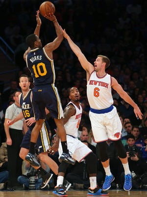 Utah Jazz point guard Alec Burks (10) shoots over New York Knicks small forward Travis Wear (6) and shooting guard J.R. Smith (8) during the second quarter at Madison Square Garden.