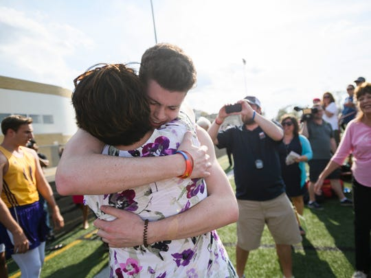 Sean English hugs his mother, Peggy, following the final race of his high-school career.