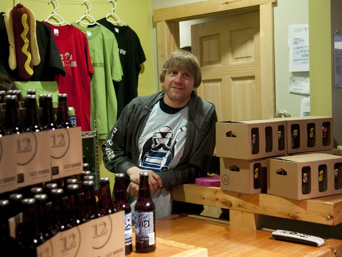 Flat 12 Bierworks professional pourer Todd Bracik stands with merchandise and four-packs of Winter Cycle Double IPA during a third anniversary party at Flat 12 Bierworks brewery on Dorman Street, Saturday, Jan. 4, 2014. The party featured tastings of over 50 of the local brewery's products.