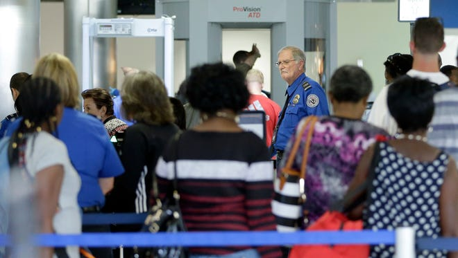 A Transportation Security Administration officer overlooks the lines as travelers prepare to be screened at a checkpoint at Fort Lauderdale-Hollywood International Airport, Friday, May 27, 2016, in Fort Lauderdale, Fla. Memorial Day weekend, the unofficial start of summer vacations for many and a busy travel period, serves as a crucial test for the TSA. (AP Photo/Alan Diaz)