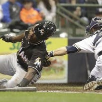 Miami Marlins' Marcell Ozuna slides safely past Milwaukee Brewers' Jonathan Lucroy at home during the third inning of a baseball game Saturday, April 30, 2016, in Milwaukee. Ozuna scored on a hit by J.T. Realmuto.