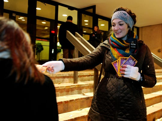 """Mormon missionary Eden Ferrin hands out a card redeemable for a free Book of Mormon as theatergoers head in to see the Tony Award-winning play, """"The Book of Mormon."""""""