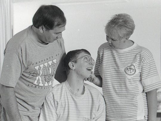 Dick Sullivan, left, and his wife Marcia have cared for their son John, middle, since he was struck by ligntning during a tournament at Forest Akers Golf Course on July 15, 1985. This photo was taken in 1991 at their home in Marlette.