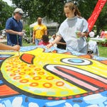 A scene from Festival Earth in 2010: Festival-goers helped to paint this mural for the Morris Area Arts Council. See more scenes from past festivals below.