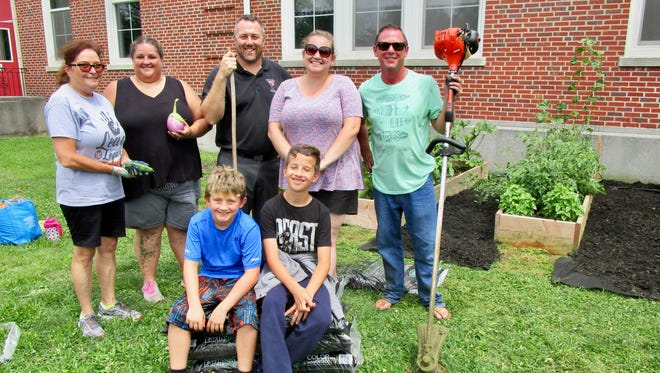 Students and staff at McManus Middle School at the school's garden on July 24. Back row, from left, are secretary Helen Koby, math teacher Christine Miskov, Vice Principal Wayne Happel, science teacher Patricia Klingert, and Principal Peter Fingerlin. In front are incoming sixth-graders Hunter DeGregorio and Adam Johnson.