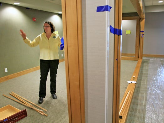 "City of Greenwood marketing coordinator Molly Laut shows a conference room, which she calls a ""fishbowl,"" at the new Greenwood City Center, 300 S. Madison Ave., Tuesday, March 11, 2014.  Greenwood bought the building which had been in foreclosure, and renovated it. Many see the city's investment as the first step in the redevelopment of downtown Greenwood."