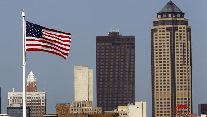 An American flag on the Capitol grounds waves in front of the Des Moines skyline in June 2013.