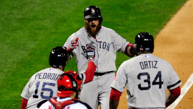 Jonny Gomes is greeted at home by Dustin Pedroia and David Ortiz after his three-run home run in the sixth inning.