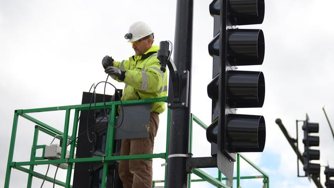 Scott Buntin, of Bodart Electric, installs traffic lights, as part of the Monroe Avenue reconstruction project in Green Bay.