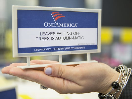 A mini sign board, given to company employees who contribute displayed sayings, held by OneAmerica employee Aly Strapulos, Indianapolis, Wednesday, March 30, 2016. Community members receive congratulations for winning entries, but company workers receive $7.50 if their joke or saying is used. Community members can email entries to corporatecommunications@oneamerica.com