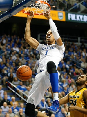 Kentucky's Skal Labissiere slams the ball home while Missouri's Kevin Puryear looks on.
