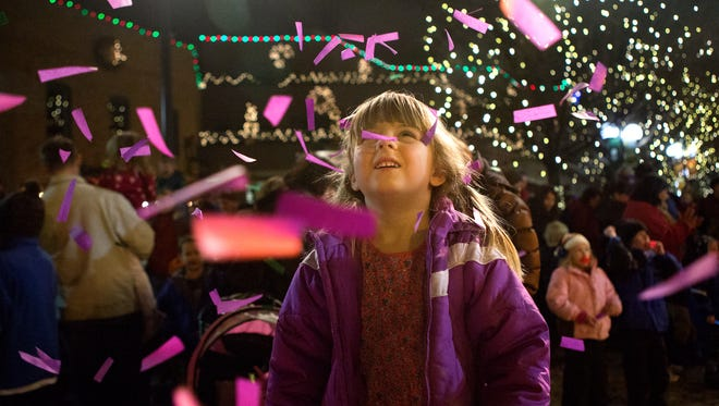 Molly Shaw, 4, is showered with purple confetti in Old Town Square during the kids' countdown at First Night in Fort Collins on New Year's Eve Tuesday, Dec. 31, 2013.