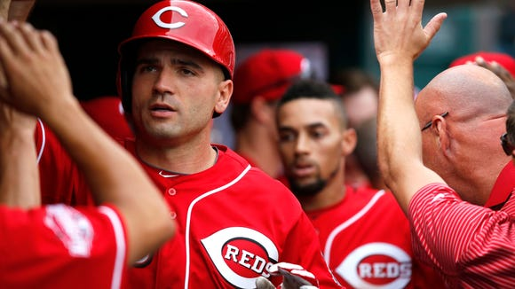 Joey Votto is welcomed back to the dugout after hitting