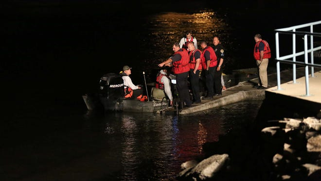 The Des Moines Police Department prepares to send a diver in to the Des Moines river to search for a boy who had gone missing earlier in the evening between the 2nd Avenue and Sixth Avenue bridges on Saturday, May 9, 2015. The boy was swimming with friends, jumped in the river and never came to the surface.