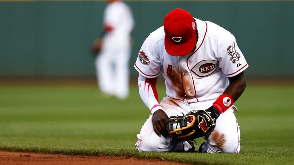 Reds second baseman Brandon Phillips takes a moment after missing a ground ball Tuesday against the Braves.
