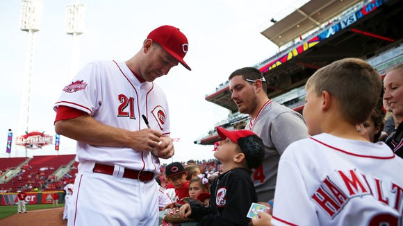 Reds third baseman Todd Frazier signs an autograph before Tuesday's game against the Braves.