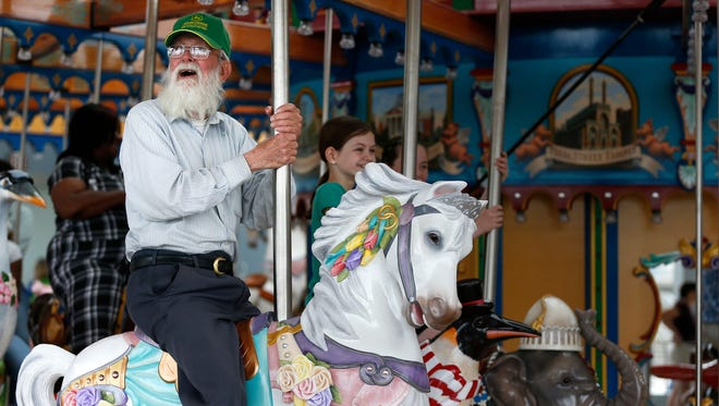 Dan Ames rides the Carol Ann's Carousel in Smale Riverfront Park on its opening day Saturday, May 16, 2015.