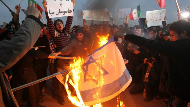 Iranian students set an Israeli flag afire during a protest to defend their country's nuclear program.