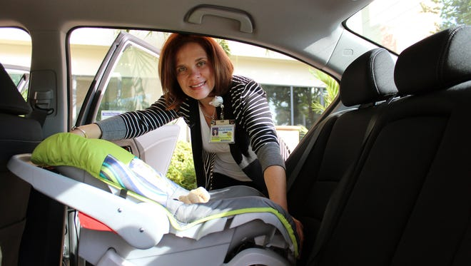 Lina Quintana, Child Advocate and Coordinator for the Kohl's Cares Program at Golisano Children's Hospital of Southwest Florida, demonstrates proper installation of an infant car seat.