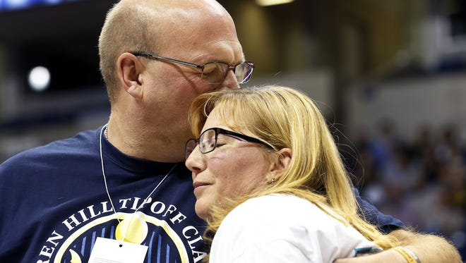 Brent and Lisa Hill embrace, while watching a video featuring their daughter, Lauren, during the halftime of the Mount Saint Joseph University and Hiram College game at the Lauren Hill Tipoff Classic at the Cintas Center Saturday, November 14, 2015.