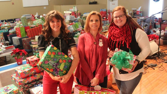 From left, Candice Payne, family resources coordinator; Sheri Weber, director of family resources; and Kaitlin Gay, family resources coordinator, stand in front of a sanctuary full of gifts for Cornelius Christmas at Trinity Presbyterian Church in Murfreesboro.