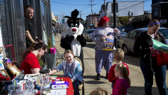Shrine Circus clowns and Sylvester from the Frame and Hang Studio Gallery greet people at the Winter Carnival In Vue on Fairfield Avenue in Bellevue Saturday, February 20, 2016.