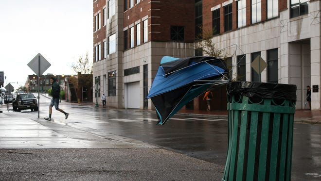 A broken umbrella is discarded as people run out of the rain while high winds and storms move into the Clarksville and Montgomery County area.