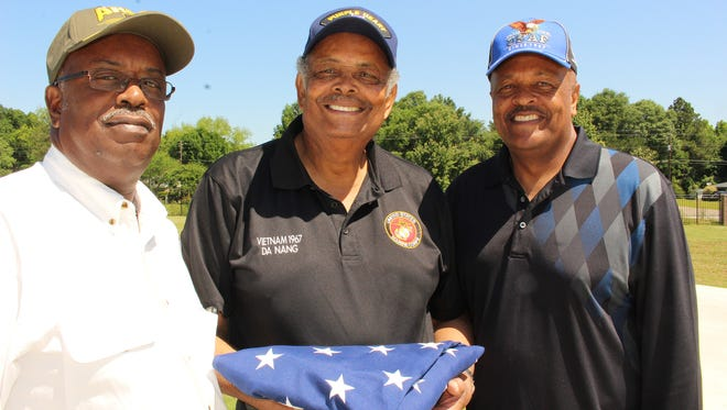 Sam Johnson, center, who was badly wounded in Vietnam, is flanked by brothers James, left, and David prior to a flag raising ceremony at Sam's new house in Selma. Alvin Benn/Special to the Advertiser.