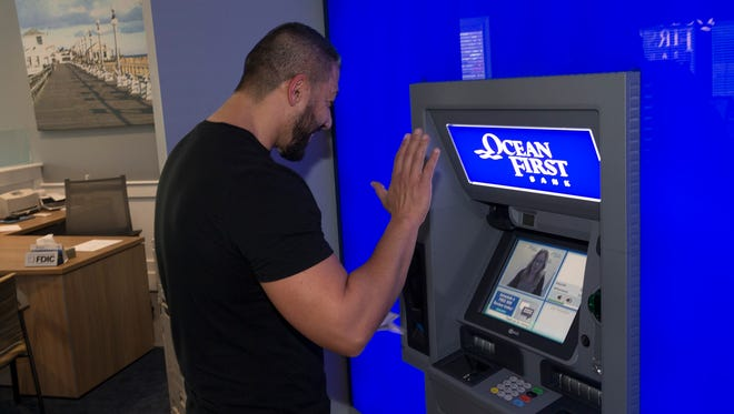 Sevket Yigiter of Jackson waves to Patty Nelson as they start their transaction using new Personal Teller Machine in the OceanFirst Bank in Jackson.
