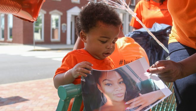 "Kyngston Clark, 1, holds a photo of his aunt Princess Clark during the ""Stop the Violence"" protest held outside of the courthouse in June 2016. The protesters wore orange for National Gun Violence Awareness Day."